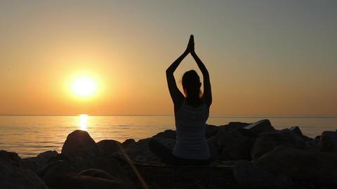 [alt video] Morning meditation, woman practices yoga on the seashore
