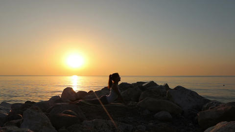 Morning meditation, woman practices yoga on the seashore Acción en vivo