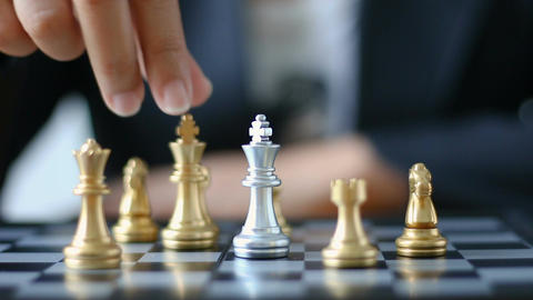 Close up shot hand of business woman moving gold king chess to kill silver king Live Action