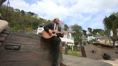 man plays guitar by wall and goes out along bridge Footage