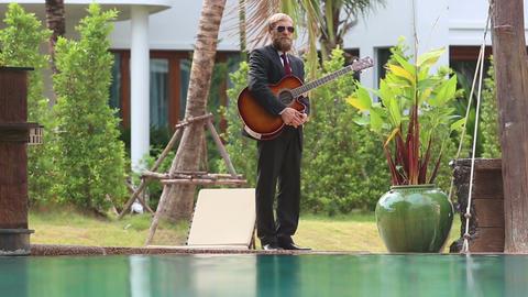 bearded guitarist in suit walk near pool Footage