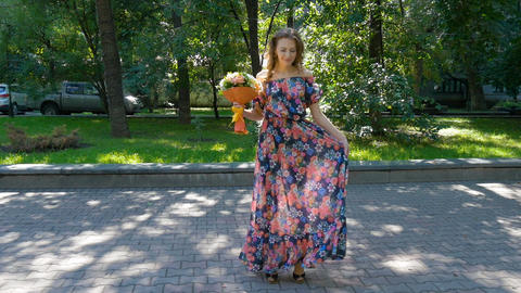 Beautiful young woman is dancing in a park with a bouquet of flowers Footage