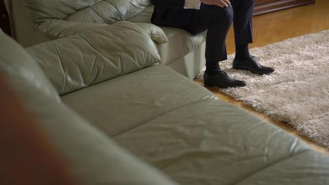 Man Ties Slack Shoes Sitting on the Sofa Footage