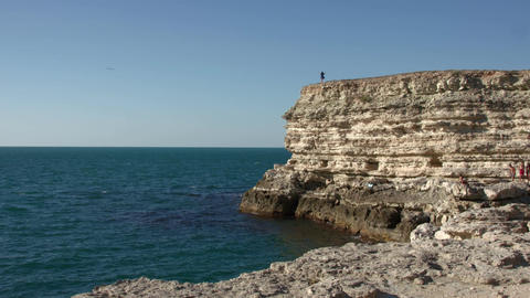 A small female figure on a rock above the sea Footage