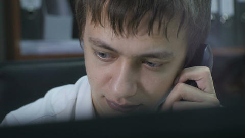 Closeup Young Manager Takes Handset in Front of Monitor Live Action