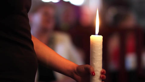 Religious ceremony, maid of honor keeps candle in hand. The candle is white 9 Footage