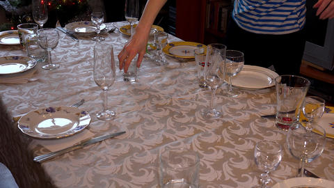 Mistress puts glasses and wine glasses on a festive table. 4K Footage
