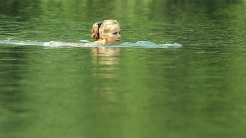 Happy young girl swims into a lake 2 Live Action