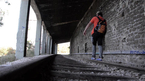 Man Walking On A Railway Track At The Exit Of A Tunnel 18 stock footage
