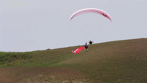 Paraglider is trying to get off the ground, while another looks at him while pre Footage