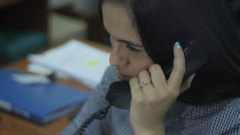 Closeup Side View Woman Talks on Telephone at Workplace Footage