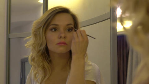Beautiful Cheerful Naughty Girl Making A Stylish Make-Up, In A Good Mood, Color Footage
