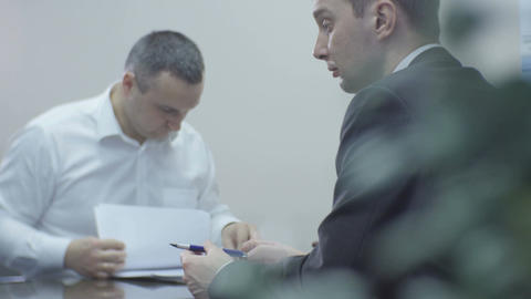 Managers Sit at Conference Table and Man Learns Offer Live Action