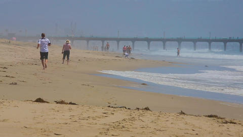 People walk on the Manhattan Beach in California Live Action