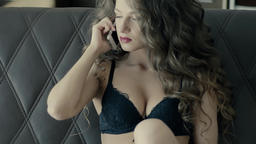 Woman Lying On Bed in Lingerie Talking On The Phone Slow Motion Footage