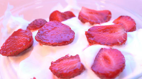 Pieces of strawberries in cream, rotating. Macro shot. looping Footage
