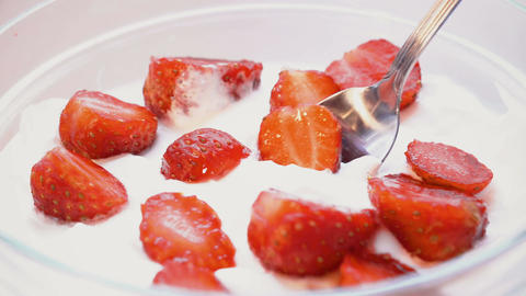 Eating strawberries with cream or yogurt by spoon, 4k. Macro shot. time lapse Footage