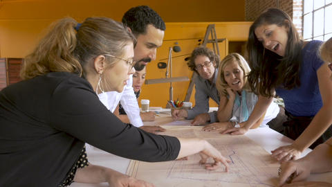 Woman boss shows her employees the architectural blueprint plans for a new Footage