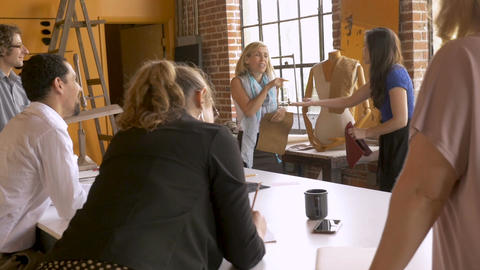 Two women presenting their idea to their coworkers at a creative business Footage