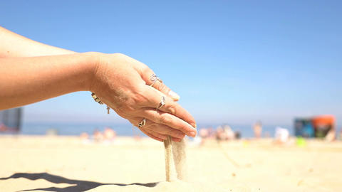Sand pouring from the hands of a woman on the beach Footage