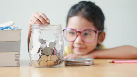 Asian little girl putting the coin into a clear glass jar on table metaphor Archivo
