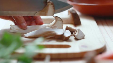 Close up shot hands of woman using kitchen knife slide cut Eringi mushroom on Archivo