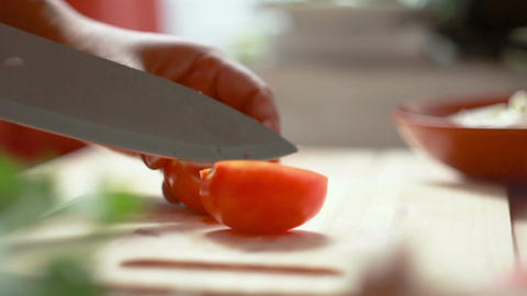 Close up shot hands of women using kitchen knife slide cut fresh tomato on Footage