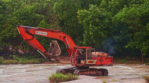 Excavator Moves along River with Rapids against Plants Footage
