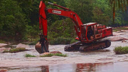 Excavator Grabbing Water from Shallow River against Jungle Live Action