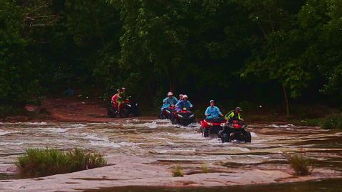 Tourists Drive All Terrain Vehicles across River against Jungle Live Action