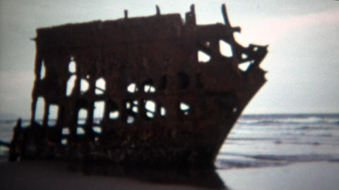 1971: Rusty broken old shipwreck beached on sandy ocean shore Footage