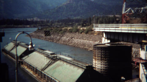 1971: Tugboat pushing big barge ship out of river industrial port Footage