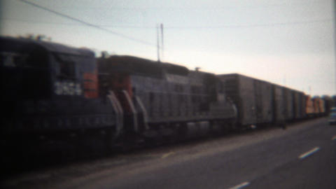 1971: Southern pacific train hauling lumber next to car driving road Footage