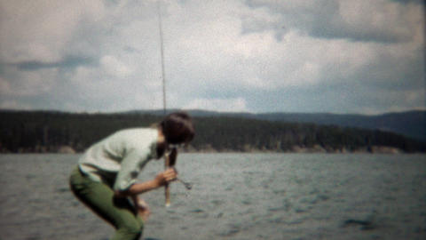 1971: Teenage girl catches trout fish in mountain lake setting Footage