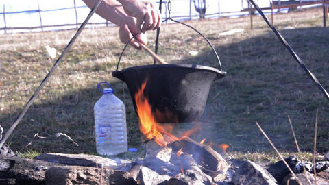 Stew made ​​traditional cauldron on wood fire. A man stew mix in with a wood Footage