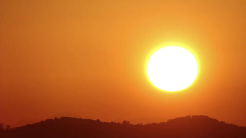 The sun rises from behind a hill. It's like a round ball, giant yellow light. On Footage