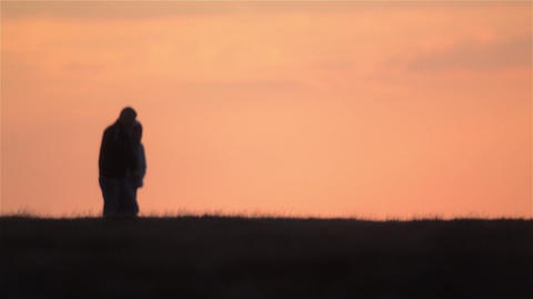 Two friends walking in a sunset light reddish cool, in an alley in the park 35 Footage