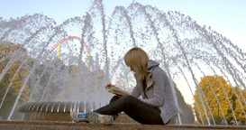 Girl reading near the fountain Footage