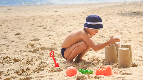Little Boy in Hat Squats Removes Bucket to Make Sand Cake Footage