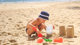 Little Boy in Hat Squats Digs Hole Fills Bucket with Sand Footage