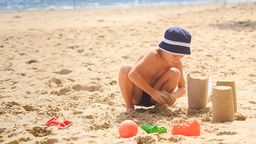 Little Boy in Hat Squats Fills Bucket with Sand on Beach Footage