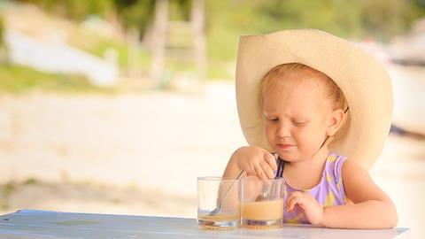 Little Girl in Large Hat Drinks Juice Looks Backwards Footage