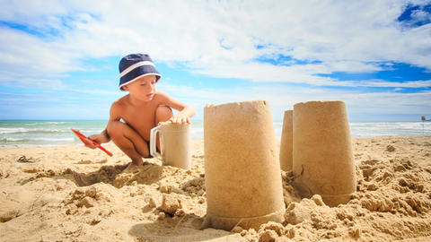 Little Boy in Hat Smoothes Sand for Cake in Plastic Mug Footage