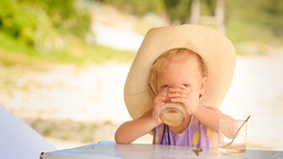 Little Blond Girl in Hat Drinks Juice from Glass Footage