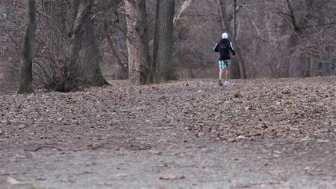Young Man Doing Running Exercise Upon Morning Forest Road. Good Video On Topics  stock footage