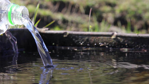 Water coming from the source through the pipe. An improvisation with a plastic b Footage