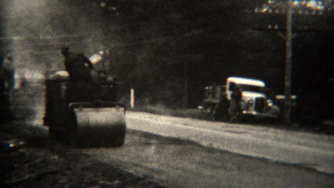 1939: Steamroller flattening newly paved asphalt road Footage