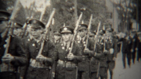 1939: Military soldiers marching with rifles in small town parade Footage