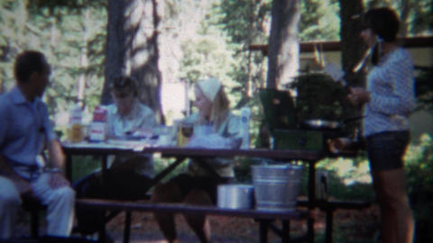 1967: Family cooking breakfast at outdoor camping picnic table Footage