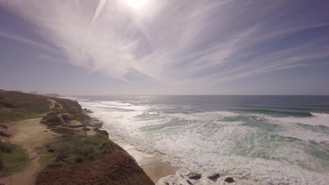 Aerial shot over ocean front cliffs showing white water waves crashing on the be Footage